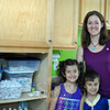 Ben's Bells Newtown team leader Jennifer Avari and her children, Hailey, 7, and Zachary, 5, stand next to a cupboard filled with beads and coins already fired, and waiting to be glazed and strung. (Crevier photos)