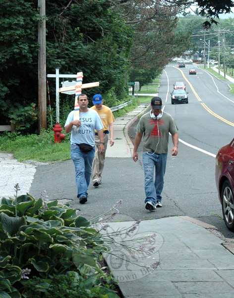 "Three men from Rochester, N.Y., strolled through Newtown on Tuesday with a mission to bring healing and prayer to residents. They carried a wooden cross that read ""Jesus Save."" One of the individuals, Domenic Danesi, on the left, nearing the top of Church Hill Road, a teacher, said they were commanded to come here by God and remind people that America's roots, at one point, were in Christ. ""We're trying to be led by the Holy Spirit but we knew we were coming to Newtown today,"" Danesi said. ""We pray before we do anything."" Danesi was accompanied by Rick, center, and Brandon, who asked to remain otherwise anonymous. Rick, a photographer, had on a T-shirt with the words ""Don't Worry — Trust God""; Brandon, a waiter, wore a hat that read ""Jesus Is Life."" The trio's stops included the Sandy Hook Fire & Rescue main station and the Newtown Volunteer Ambulance Corps facility. They have, they said, undertaken similar missions in parts of New York State as well as in Michigan. (Hicks photo)"