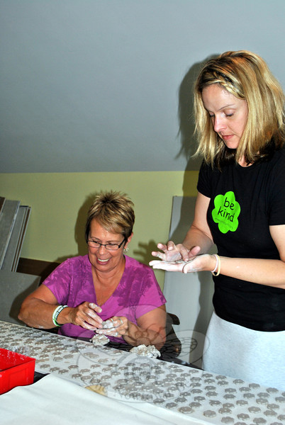 Mary Ann Cantor, seated, and Jodie Adolfson make Kindness Coins, in preparation of the grand opening of Ben's Bells Newtown, on July 13. Guests on July 13 can choose to glaze the coins, which will eventually be distributed to area schools, or make or glaze original beads for Ben's Bells. (Crevier photos)