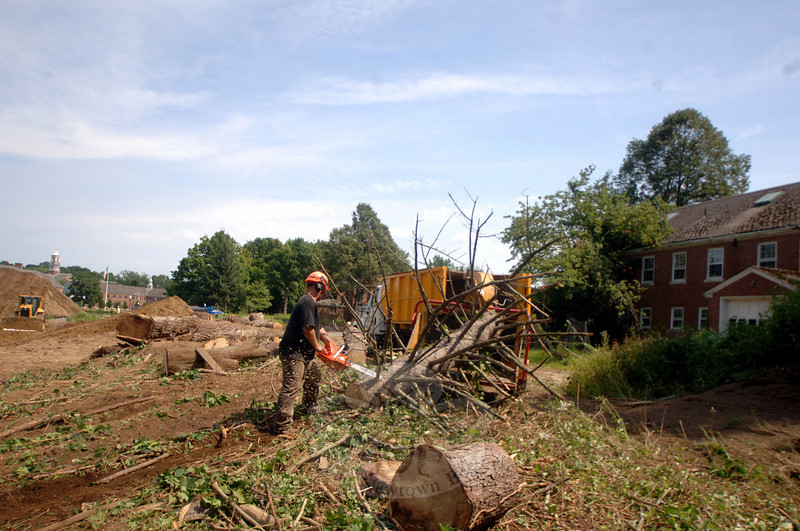 Erik Barrett removes tree limbs before sending the trunk through a chipper. (Bobowick photo)