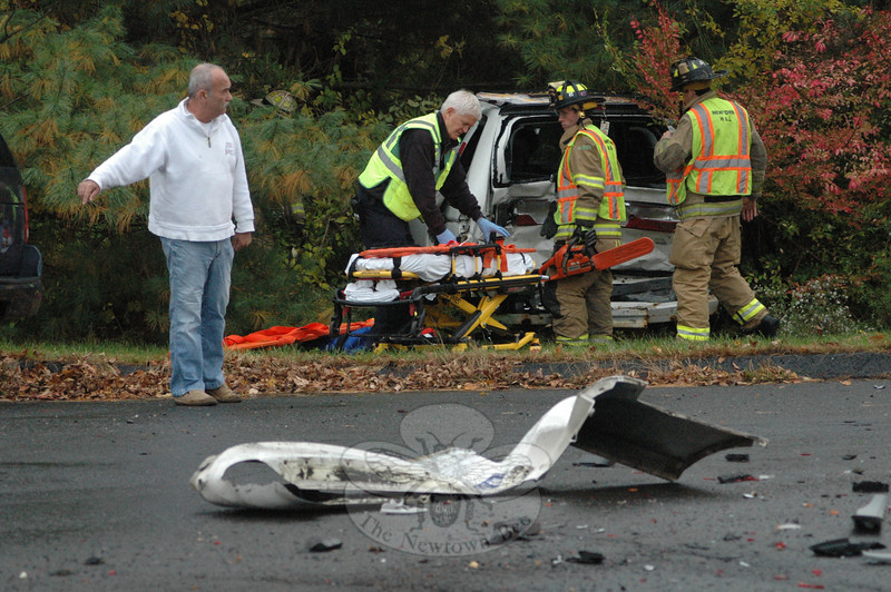 Debris from a heavily damaged minivan frames the view of emergency crews as they prepare to remove two people from that vehicle which was heavily damaged in a rear-end collision on Mt Pleasant Road at its intersection with Taunton Lake Road at about 4:30 pm on October 23. Police said motorist John Spies, 52, of 5 Taunton Ridge Road, who was driving a 2000 Honda Odyssey minivan westward on Mt Pleasant Road in wet conditions, stopped in preparing to make a left turn onto Taunton Lake Road. While attempting to stop, westbound motorist Adam Bova, 38, of 98 Hanover Road, who was driving a 2004 Ford Explorer SUV, went into a skid and then struck the rear end of the Honda, police said. The impact pushed the minivan into a wooded area. Newtown Volunteer Ambulance Corps members transported John Spies and passenger William Spies, 10, of the same address, to Danbury Hospital for treatment of injuries, police said. Hook & Ladder firefighters responded to the accident. Police said they issued Bova an infraction for following too closely. (Gorosko photo)
