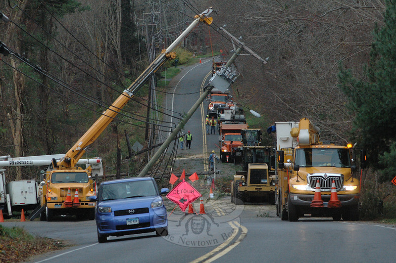 Several Connecticut Light and Power Company (CL&P) and state Department of Transportation (DOT) crews joined forces on Wednesday afternoon in working to clear a major road blockage on Sugar Street (Route 302) at its intersection with Boggs Hill Road and West Street. The high winds of Storm Sandy early this week had caused the electrical equipment to fail. (Gorosko photo)