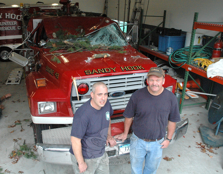 Pete Barresi, left, and Chuck Kilson, both of whom are Sandy Hook Volunteer Fire & Rescue Company firefighters, this week recalled an accident that occurred on Monday on a fire call during Storm Sandy, in which a massive tree fell onto the cab of a fire truck occupied by Mr Kilson, who narrowly escaped injury in the incident. (Gorosko photo)