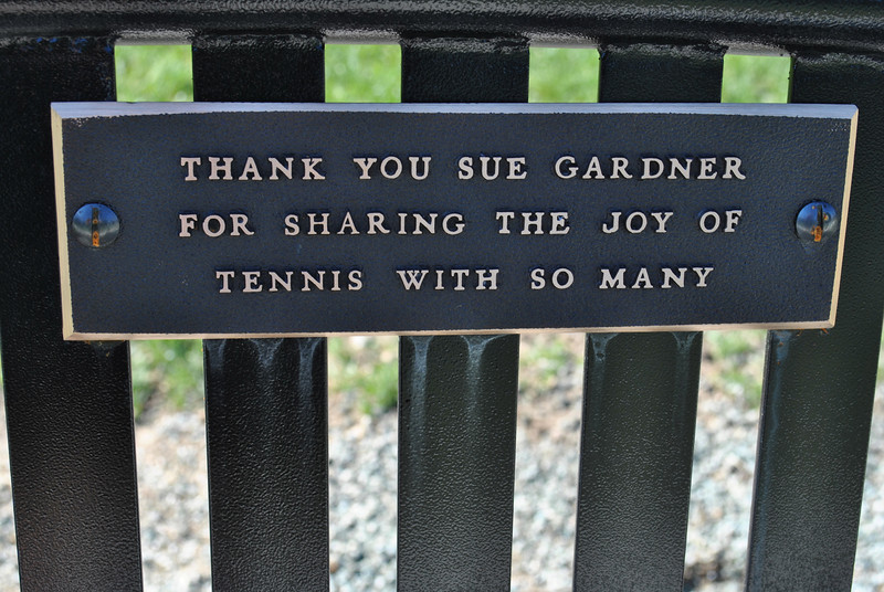 The plaque attached to the bench honoring Sue Gardner speaks to her dedication to tennis students over the years. (Crevier photo)