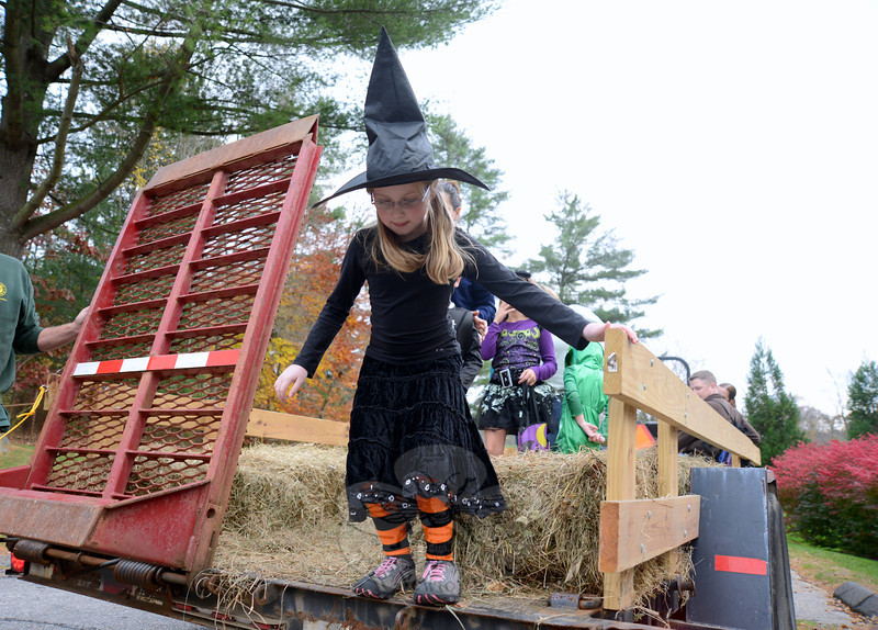 Skylar Lewis and her tall black hat stop off the hayride during a Halloween party at Dickinson Park.  (Bobowick photo)