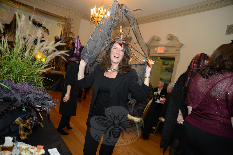 Cyndy DaSilva wears Catching Fall, a decorative hat designed by artist Gabrielle Amucke. As she worked her way through the Alexandria Room buyers made their bids for the hat. (Bobowick photo)