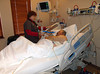 DOING MY BREATHING EXERCISES<br /> Here's my respiratory therapist, Tammy, torturing me with regular breathing exercises to build up my collapsed lung back into shape. It hurt quite a bit, but better that than a bad case of pneumonia on top of everything else. I still have that torture device.