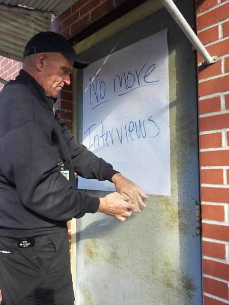Newtown Volunteer Ambulance crew member Marty Folan hangs a sign on one of the doors to the local ambulance headquarters Wednesday afternoon informing the media that the volunteers would not be granting any additional interviews after an onslaught of requests that began pouring in hours after the news of the Sandy Hook shooting began circulating December 14.(Voket photo)