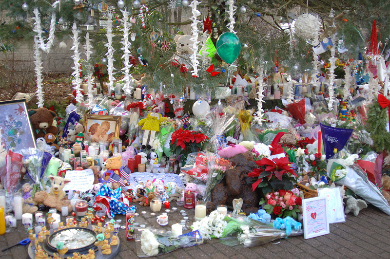 Thousands of hopes and wishes in the form of flowers, candles, and more have been placed beneath the tree in Sandy Hook Center. (Bobowick photo)