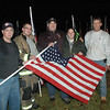 To memorialize the 26 people who died in the December 14 shooting incident at Sandy Hook Elementary School, members of the Hawleyville Volunteer Fire Company on a rainy Tuesday night positioned 26 illuminated US flags on a lawn near the Hawleyville Firehouse. The flags are stationed alongside Hawleyville Road (Route 25). Pictured, from left, are Chief Joe Farrell, Firefighter Marty Basso, Captain Don Digioia, Firefighter Sarah Hayes, and Firefighter Don Hutchins. The Kiwanis Foundation of Greater Danbury donated the 26 flags. (Gorosko photo)