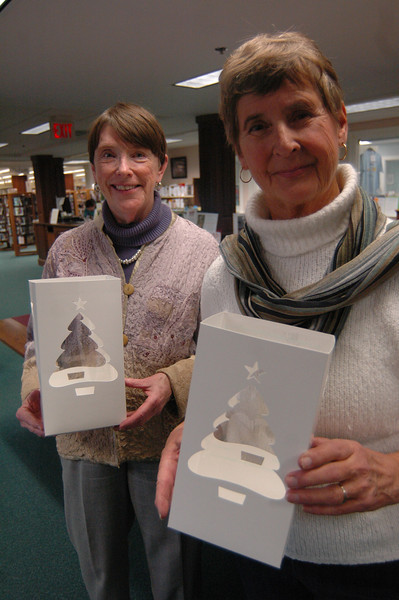 Curtis Packaging donated 3,000 luminaria boxes — the same ones that are traditionally used for the Ram Pasture tree lighting — for residents free of charge, and Diana Johnson, right, and Janet Woycik, helped distribute them at C.H. Booth Library on Tuesday, December 18, free of charge. Ms Johnson also said the Yankee Candle offered tea lights for residents to use with the luminarias. The boxes were for anyone who would like them in conjunction for a Friday night memorial/candlelight vigil that is being planned. (Hallabeck photo)