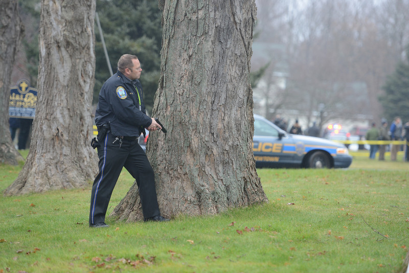 A threat during a St Rose of Lima service Sunday, December 16, prompted authorities including Newtown police officer William Hull to draw weapons and position themselves for an emergency. State police also responded, and with long rifles ready, checked the area. (Bobowick photo)