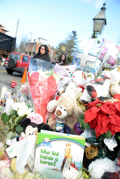 Crinkling cellophane wrappers around bouquets, bundles of toys and stuffed animals, children's books, and more have begun to overflow from places where memorials have emerged in town. (Bobowick photo)