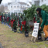 Shelja Patel props up a sign to let residents know the festive trees are in memory of Sandy Hook's victims. (Bobowick photo)