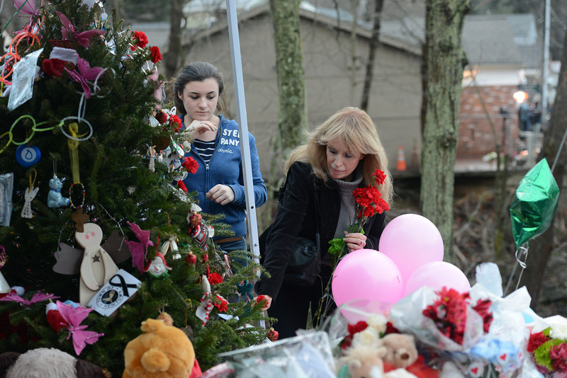 Out of town residents Sierra Mayerson, left, and her grandmother Joan Burke add roses to the growing memorial contributions that have emerged in Sandy Hook Center and elsewhere in town as gifts and more pour in. (Bobowick photo)