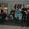 Opus Pocus, a musical group made up of area musicians, from left, Bruce Alexander on bass, Al George on drums, Bob Place on vocals and guitar, and Ted Jeffries on vocals and tenor ukulele entertained a full house at the Newtown Senior Center, Thursday, December 13, with a program of jazz and swing standards, and plenty of holiday tunes. The year-old band has performed at various other venues in Brookfield, Danbury, and Newtown. Unable to resist the music, Commission on Aging member Karen Aurelia, right, joined Senior Center member Beverly Panettiere and others on the dance floor. Senior Center members were treated to a buffet of appetizers and desserts following the program. (Crevier photo)