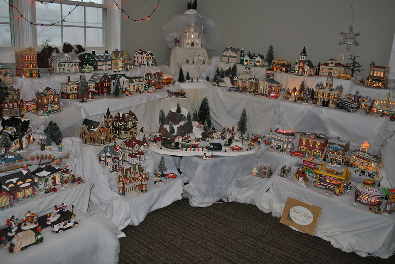 "Bill and Kathy Hurley of Newtown have devoted one entire room this holiday season to Mr Hurley's Department 56 Snow Village collection. Many pieces received over the years as gifts, or found at flea markets and tag sales, reflect the Hurley's personalities, such as the ski village, the garage sale scene, and ""Big Bill's Garage."" A Hawley Pond scene, complete with tiny luminaria, is one of the featured scenes this year. Mr Hurley has been collecting pieces since 1986, but most years, space does not allow them to set up all of the pieces. In addition to the 91 lit pieces, plus accessories and characters that fill tiered levels in the room, additional pieces adorn the living room mantel and entry way. The village took the Hurleys nearly three weeks to set up, working on and off, and they expect to leave it up until February for friends and family to admire.  (Crevier photo)"