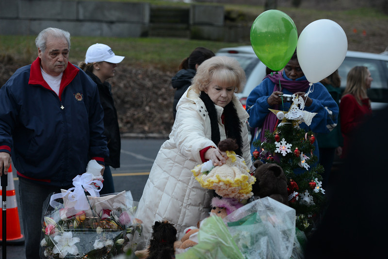 Dolls, stuffed animals, flowers, candles, and angels are among the many items added to memorials emerging in town. (Bobowick photo)