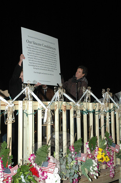 As David Paine looked on at a December 21 candlelight vigil at Fairfield Hills, First Selectman Pat Llodra holds aloft a poster symbolizing the multitude of people who had signed a letter of condolence to the town over the December 14 shooting deaths at Sandy Hook Elementary School. Mr Paine helped organize the digital sympathy card. (Gorosko  photo)