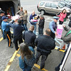 "Volunteers unloaded a storage bin filled with dolls, games, and toys that had been shipped from Bergen County, N.J., on December 21 to Newtown. The bin was part of the large collection of toys that were then distributed from Edmond Town Hall the following afternoon. ""Many different patches here, but one mission,"" one organizer said of the effort by a number of New Jersey police departments to bring so many gifts to the residents of Newtown. The Newtown Volunteer Task Force is still looking for volunteers to help organize, sort, and pack similar donations, which are now being sent to a warehouse space on Simm Lane. (R. Scudder Smith photo)"