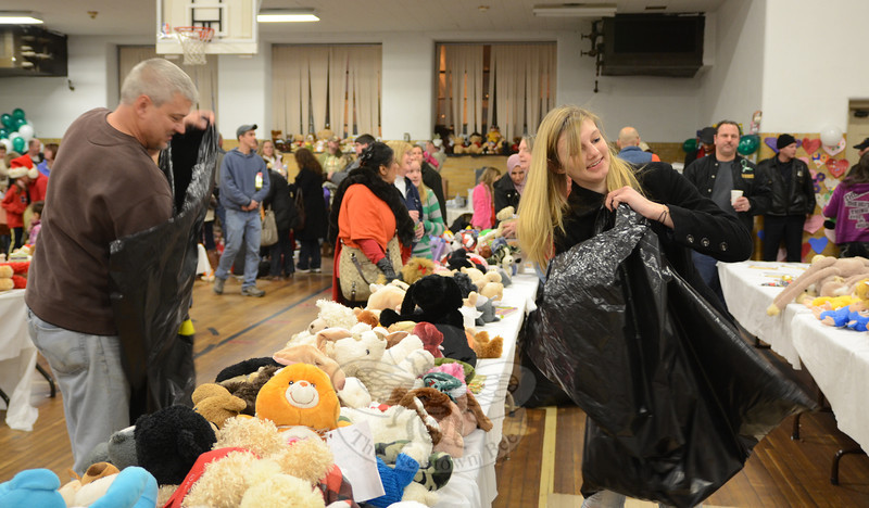 The father-daughter team of Michael and Marysa Audet work efficiently restocking the few bare areas of the Edmond Town Hall gym that were momentarily empty of toys during a communitywide giveaway event December 22. (Voket photo)