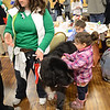 Sarah Katrulya and her therapy dog Oreo comfort toddlers Caroline and Cassidy December 22 at Edmond Town Hall, while Cheryl Stenz and sons Will and Jack posed for an Associated Press reporter who also attended the townwide toy giveaway. (Voket photo)