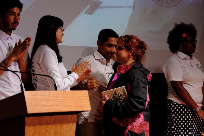 Claudia Girón recibe una pieza del mosaico para la Fundación Manuel Cepeda.