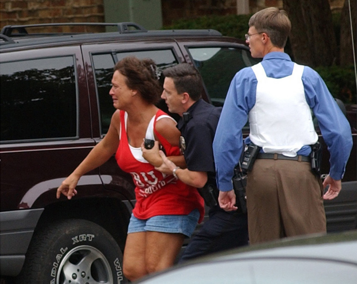 E.L. HUBBARD/JOURNALNEWS<br /> A woman (in red) who had been held hostage for several hours Monday at the Camelot East apartments in Fairfield is led to safety by Fairfield police officers.