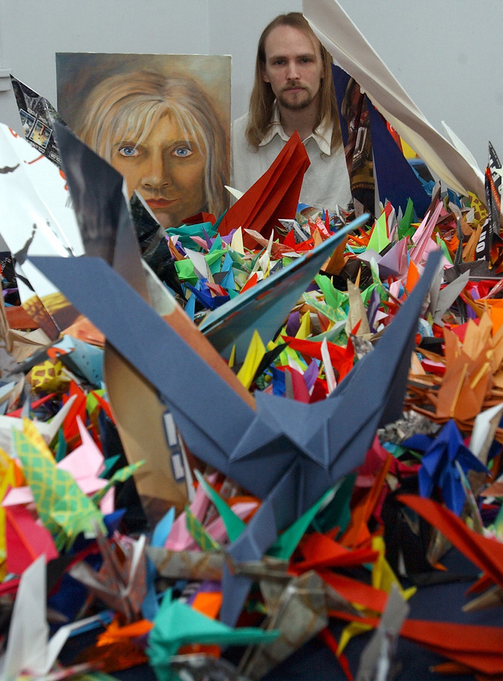 E.L. Hubbard/Journal-News<br /> David Dotson assembled 1,000 paper origami cranes to be used as a fund raiser for his friend Katie Clements, whose portrait he holds, which he also painted.