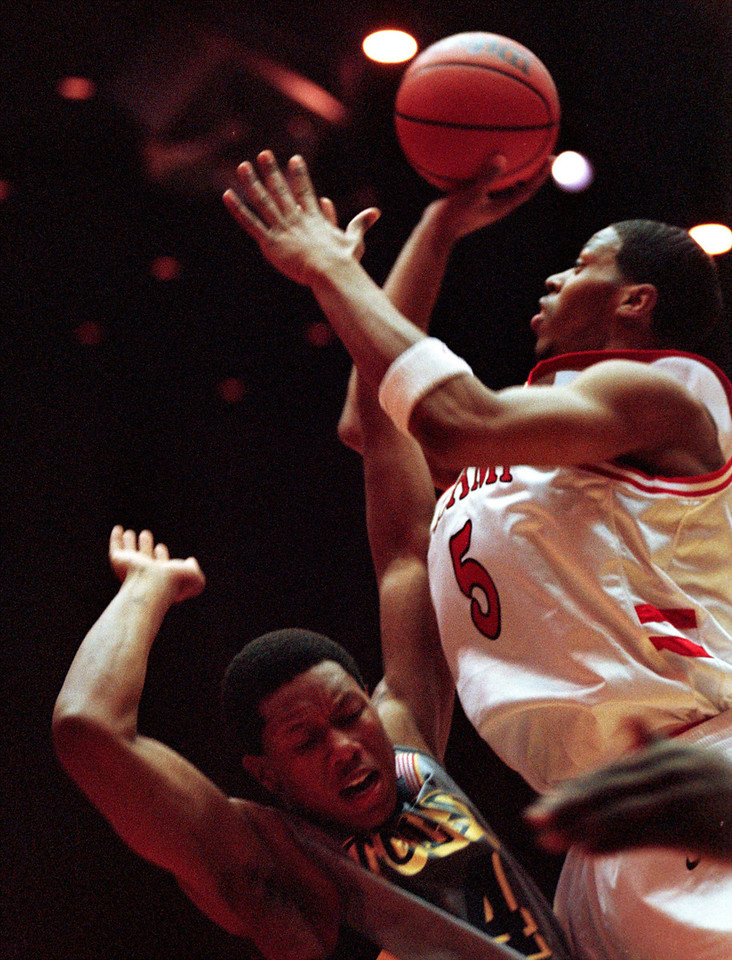 E.L. Hubbard/Journal-News<br /> Miami Redhawk's guard/forward Juby Johnson shoots over Toledo Rocket's forward Milo Kirsh in the first half of their game Saturday at Millett Hall in Oxford.