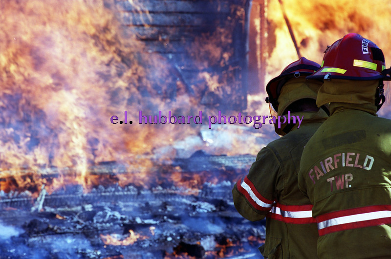 E.L. Hubbard/Journal-News<br /> Fairfield Township fire fighters watch over a house fire Saturday on Seward Rd.  The vacant home was burned by the department for training.