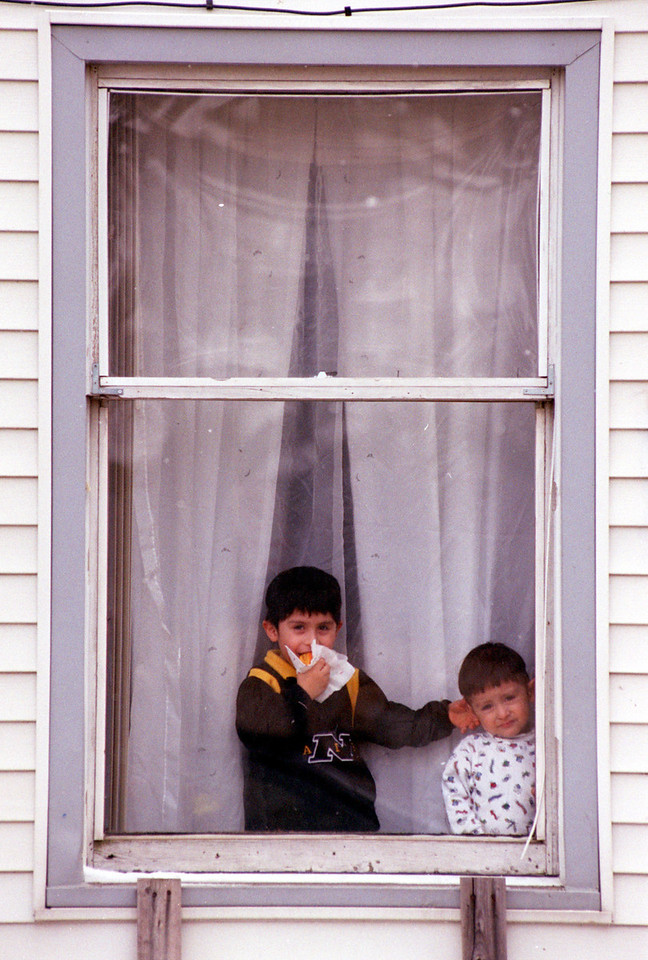 E.L. Hubbard/Journal-News<br /> Cristian Jacinto, 5, pulls on the ear of his little brother Oscar, 2, while also eating a sandwich Wednesday as the two stand in the window of their 4th St. home.  Colder temperatures which returned to the area helped keep the boys inside.