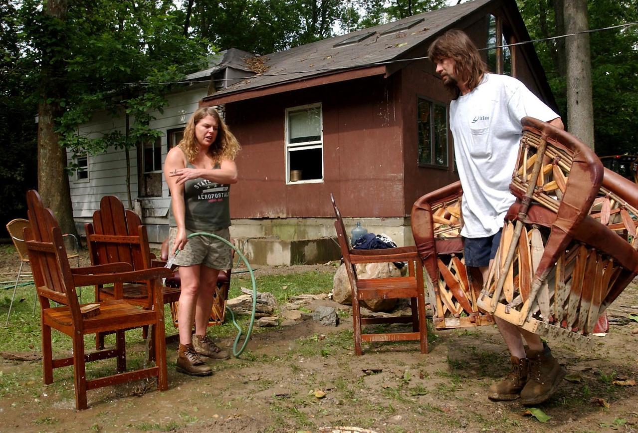 Homeowner Amanda Spicer and her boyfriend Thomas Hobbs clean mud from some of their salvagable furniture at their Warwick Rd. home Wednesday, 6/18/03.