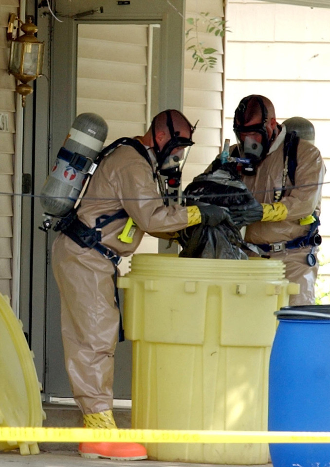 Two men from the Butler County Sheriff's Emergency Services Unit remove a propane tank from a home where a suspected meth lab was in operation in St. Clair Township Friday, 7/18/03.