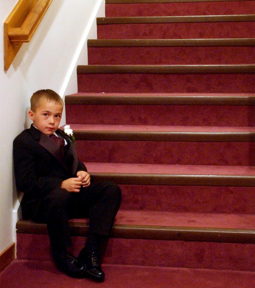 E.L. HUBBARD/JOURNALNEWS<br /> Ring bearer Lenny Hollandsworth, 7, waits on the steps for the start of the Isaacs-LeFevre wedding Saturday, 6/14/03.