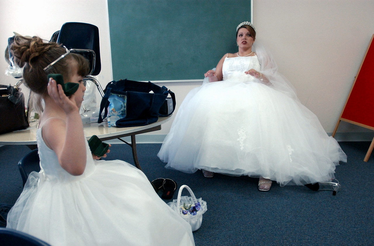 E.L. HUBBARD/JOURNALNEWS<br /> Flower girl Tara Griffin, 7, and bride-to-be Nicole Isaacs take a break after pictures before the start of the wedding Saturday, 6/14/03.