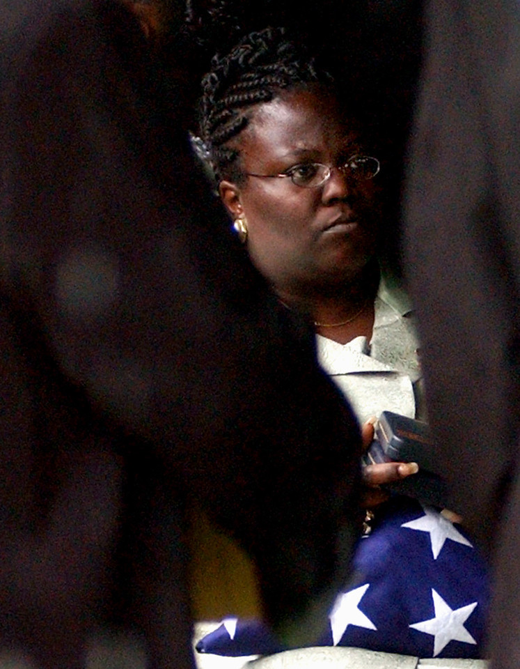 E.L. HUBBARD/JOURNALNEWS<br /> DaVonna Rockhold, center, wife of slain U.S. Army Pfc. Marlin Rockhold, holds her late husband's service medals and the flag from his casket after graveside services at Greenwood Cemetery Saturday, May 17, 2003, in Hamilton, Ohio. Pfc. Rockhold was killed by a sniper in Baghdad, Iraq on May 8.