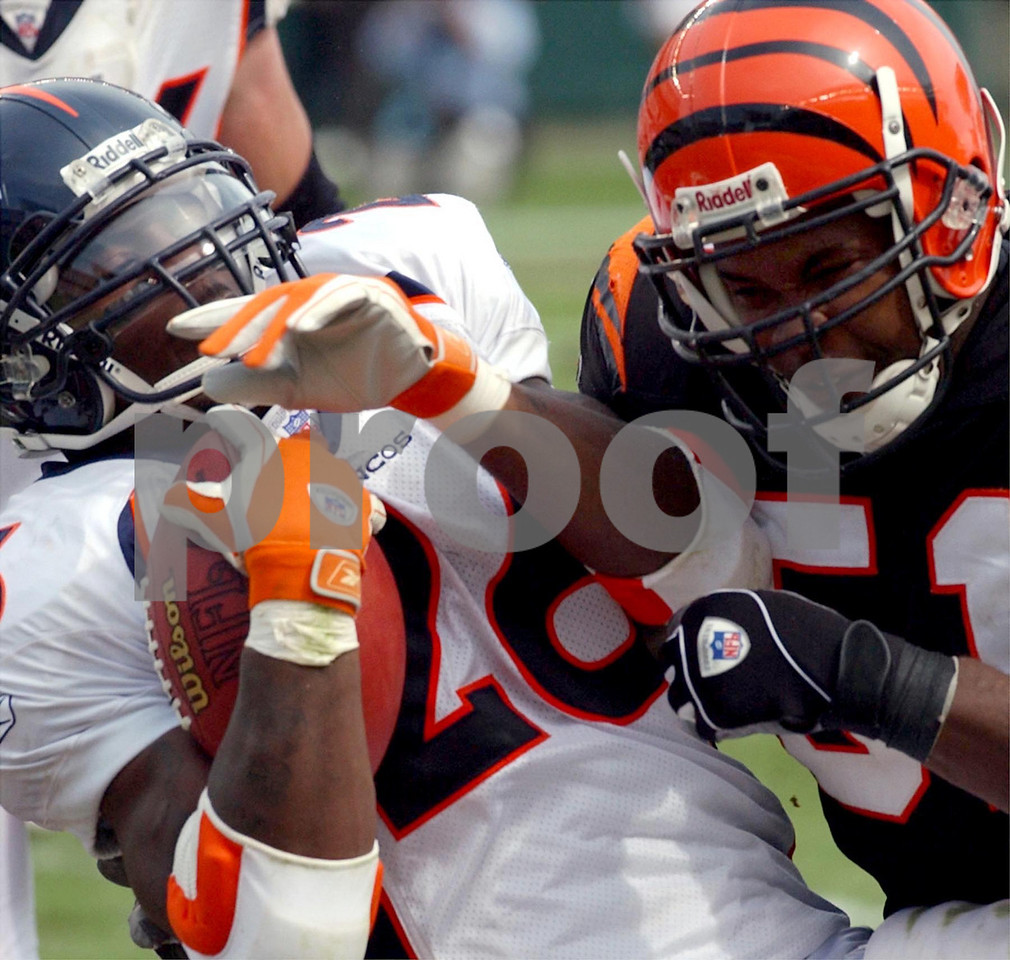 Denver Broncos running back Clinton Portis is stopped by Cincinnati Bengals middle linebacker Kevin Hardy in the second half at Paul Brown Stadium Sunday, 9/07/03.