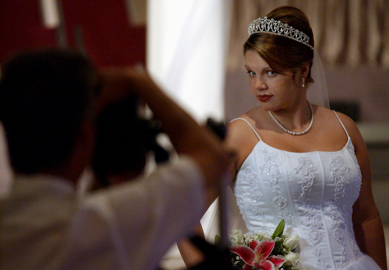 E.L. HUBBARD/JOURNALNEWS<br /> Bride-to-be Nicole Isaacs poses for wedding photographer Dennis Heidelberg before the ceremony at Hamilton Christian Center Saturday, 6/14/03.