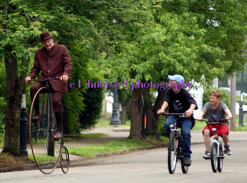 E.L. HUBBARD/JOURNALNEWS<br /> Del Nichols, of Findlay, Ohio, is followed by two youngsters on modern bikes as he pedals his 1887 Kennedy highwheeled bike down 8th St. in Hamilton, Ohio Sunday, 5/18/2003 during the Dayton Lane May Promenade of historical homes.