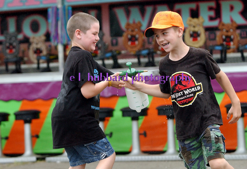 E.L. HUBBARD/JOURNALNEWS<br /> Travis Nuss, 8, of Liberty Township, and Joshua Niederman, 9, of Hamilton chase each other in circles with a water sprayer Wednesday, 07/27/05 at the Butler County Fair.