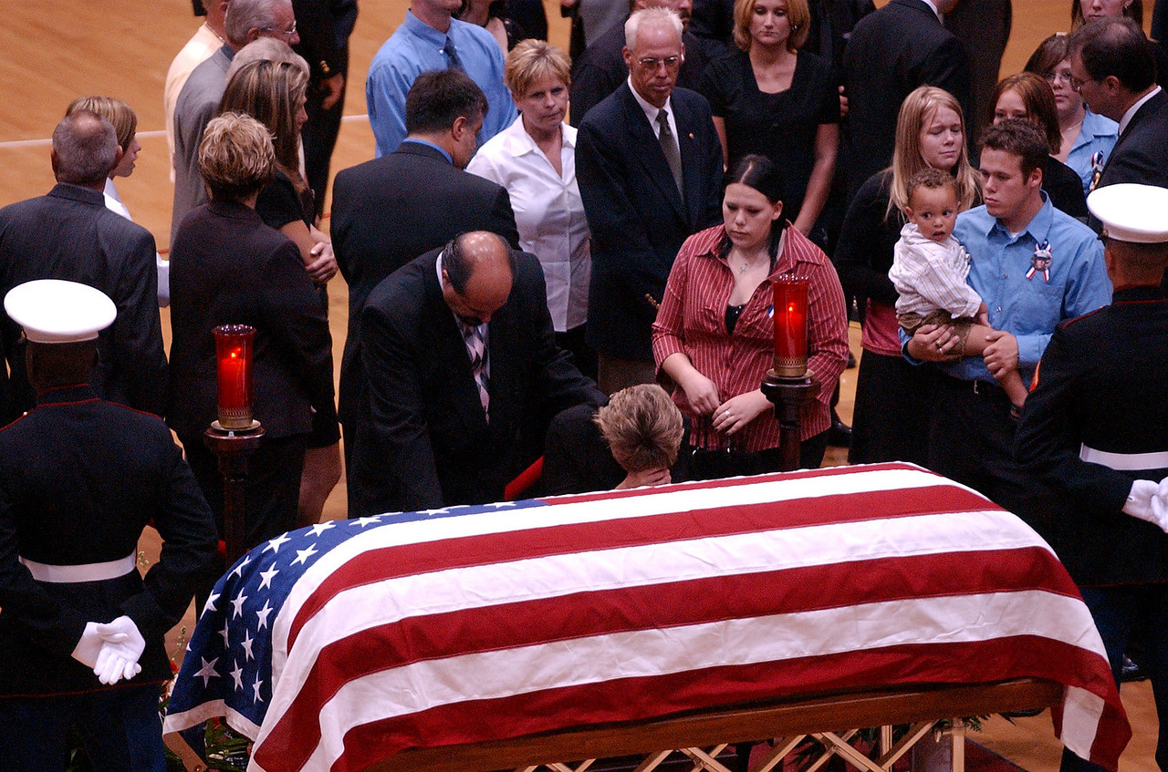 E.L. HUBBARD/JOURNALNEWS<br /> Members of Lance Cpl. Timothy Bell, Jr.'s family mourn at the casket of Lance Cpl. Michael Cifuentes in the arena at Fairfield High School Sunday, 08/14/05. The Bell family came directly from funeral services for Bell at Lakota East High School.