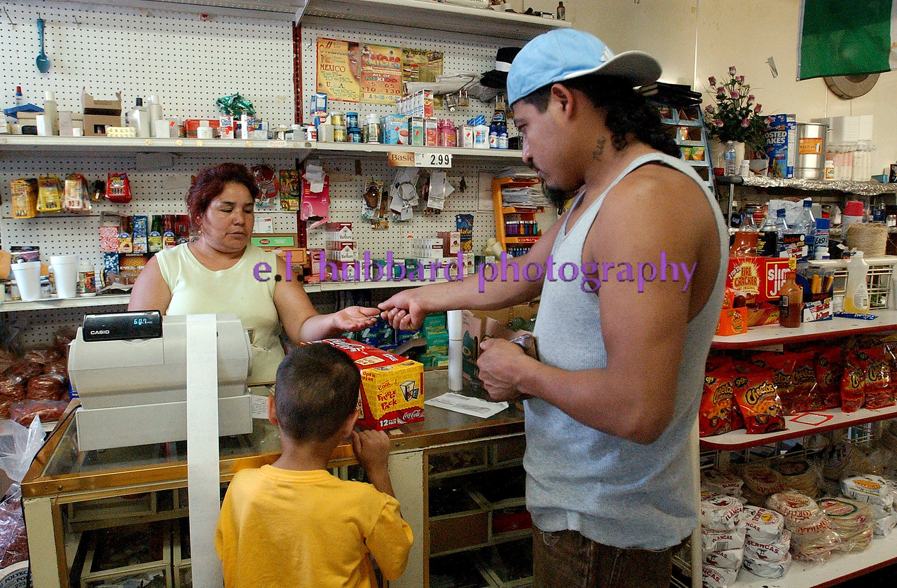 Ramona Ramierez waits on customer Guadalupe Oliva and his son, Gabriel, 5, in her East Ave. store Saturday, 06/25/05.<br /> Photo by E.L. HUBBARD