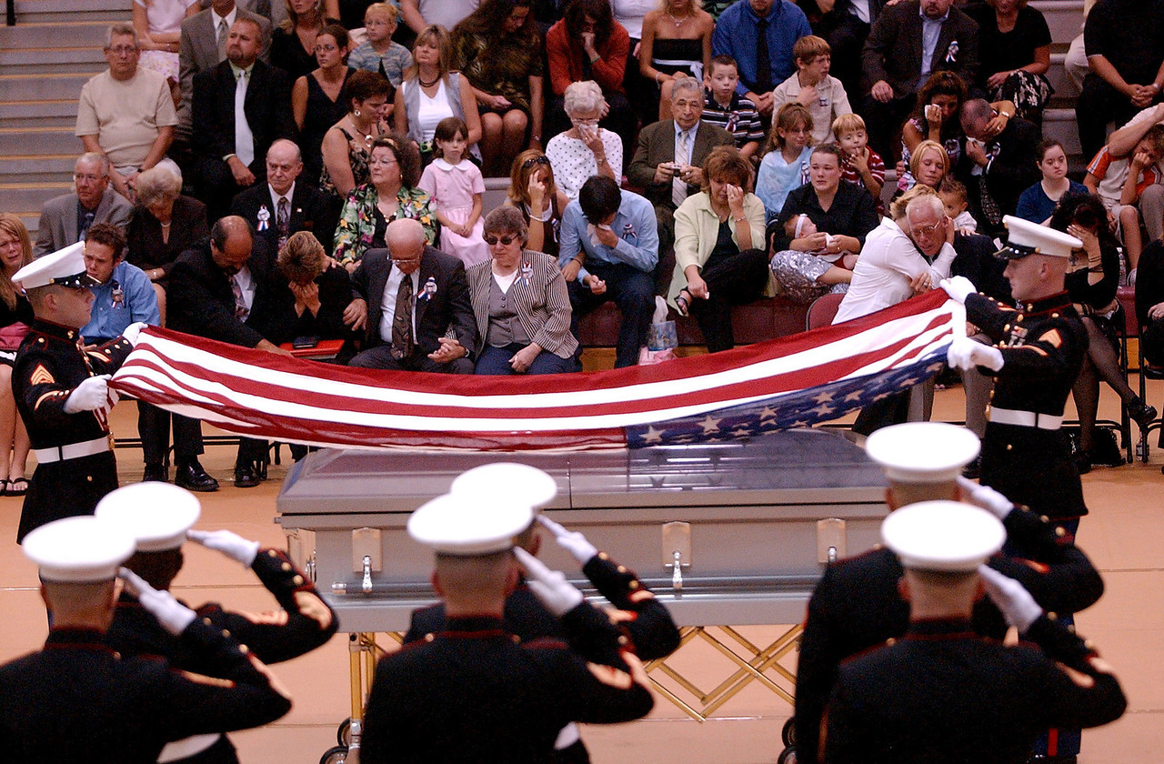 E.L. HUBBARD/JOURNALNEWS<br /> The parents of Lance Cpl. Timothy Bell, Jr., his mother on the left and his father on the right, are comforted as two Marines raise the flag from his casket and a 21-gun salute is fired during his funeral at Lakota East High School in Liberty Township, Ohio Sunday, 08/14/05.