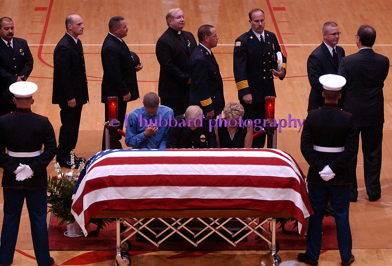 E.L. HUBBARD/JOURNALNEWS<br /> A firefighter and his family pray at the casket of Lance Cpl. Michael Cifuentes as other firefighters offer condolences to the father, Gregory Cifuentes, far right, during visitation at Fairfield High School Sunday, 08/14/05.