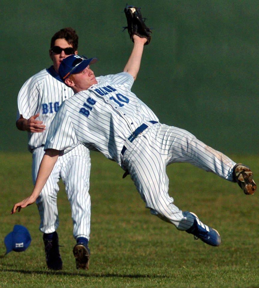 E.L. HUBBARD/JOURNALNEWS<br /> Big Blue second baseman Sean Dixon (10) loses his feet while trying to grab a fly ball in the second inning against Oak Hills at Stang Field Wednesday, 03/30/05. The batter was safe at first after the umpire ruled the ball touched the ground when Dixon landed. Coming in for backup is right fielder Jason Bierly.