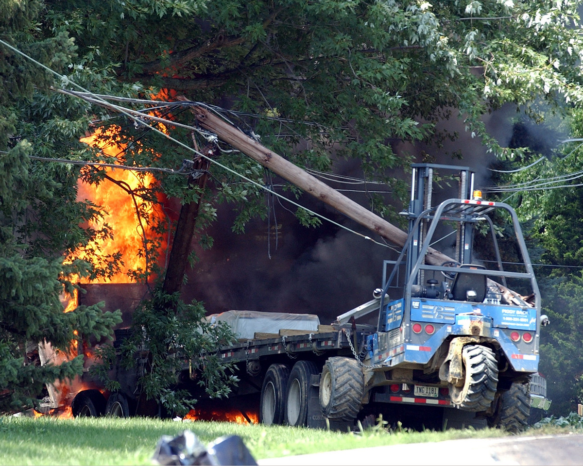 E.L. HUBBARD/JOURNALNEWS<br /> A truck involved in a crash on West Elkton Rd. north of Trenton Oxford Rd (73) burns under the broken utility pole and downed wires where it stopped after colliding with a car Thursday, 07/21/05.