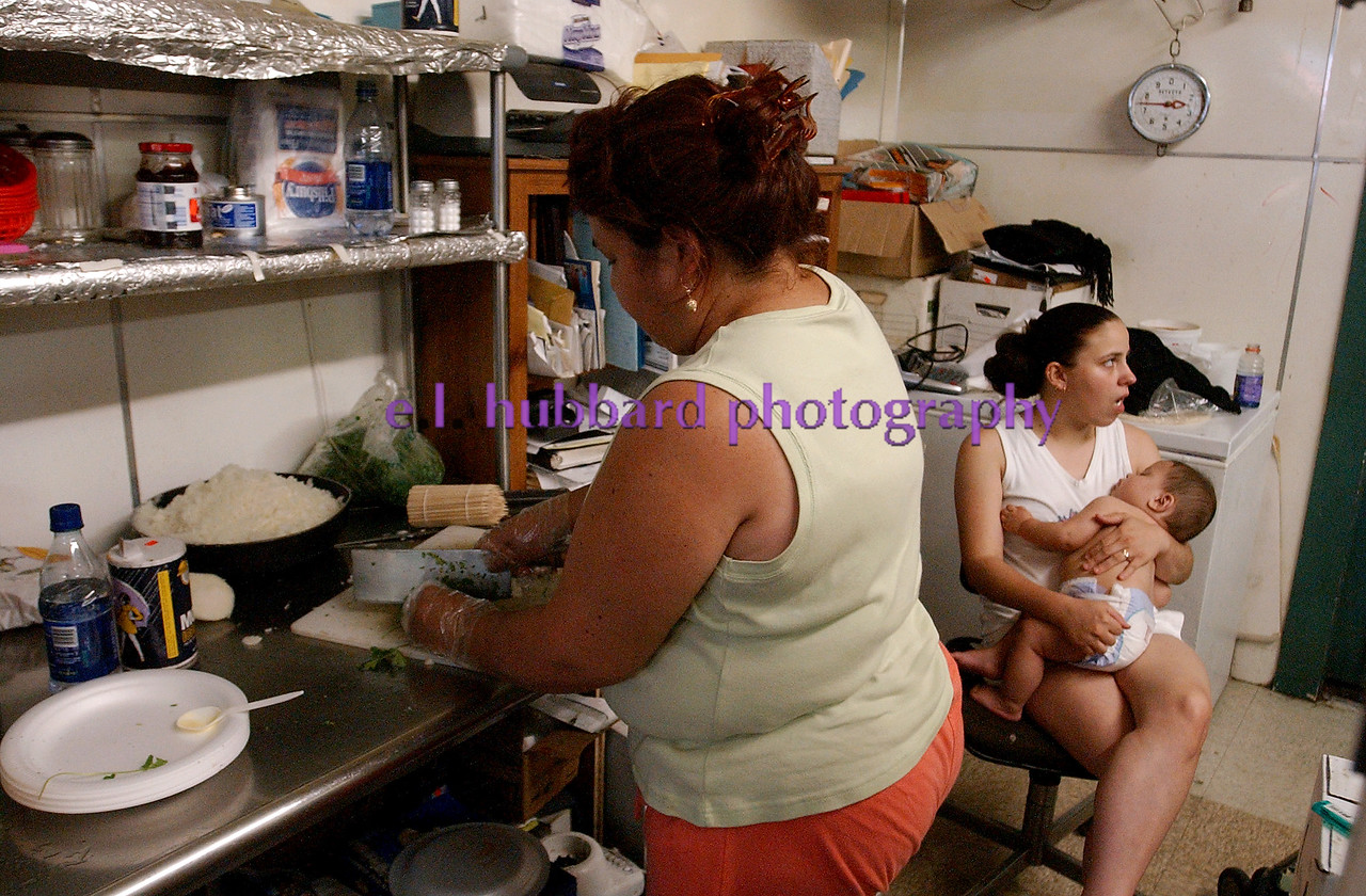Ramona Ramierez prepares one of the meals she sells as her friend Brittany Emerson holds her son, Christian Becerra, 8 months, in the East Ave. store Saturday, 06/25/05.<br /> Photo by E.L. HUBBARD