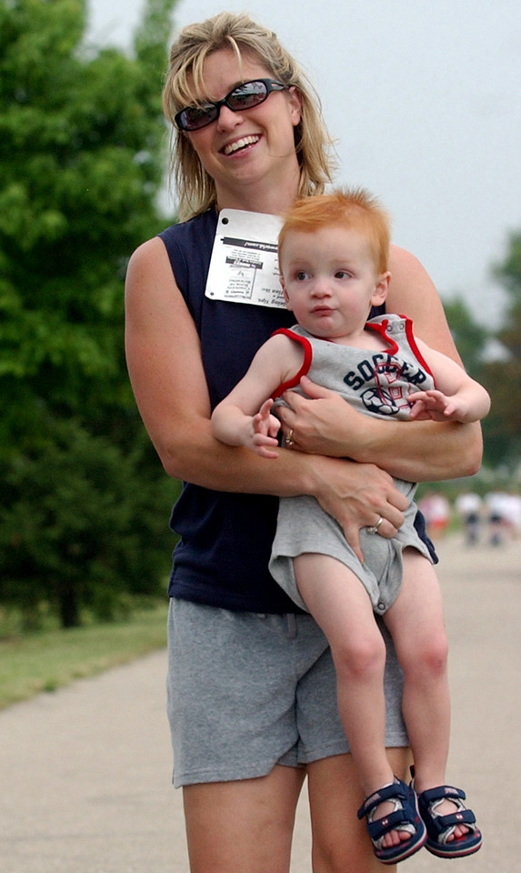 Amanda Hook((cq)) carries her son, Gavin((cq)), 20 months, across the finish line of the 5K run/walk at Liberty Park((cq)) during the 4th of July Festival Tuesday, 07/04/06. Staff photo by E.L. Hubbard