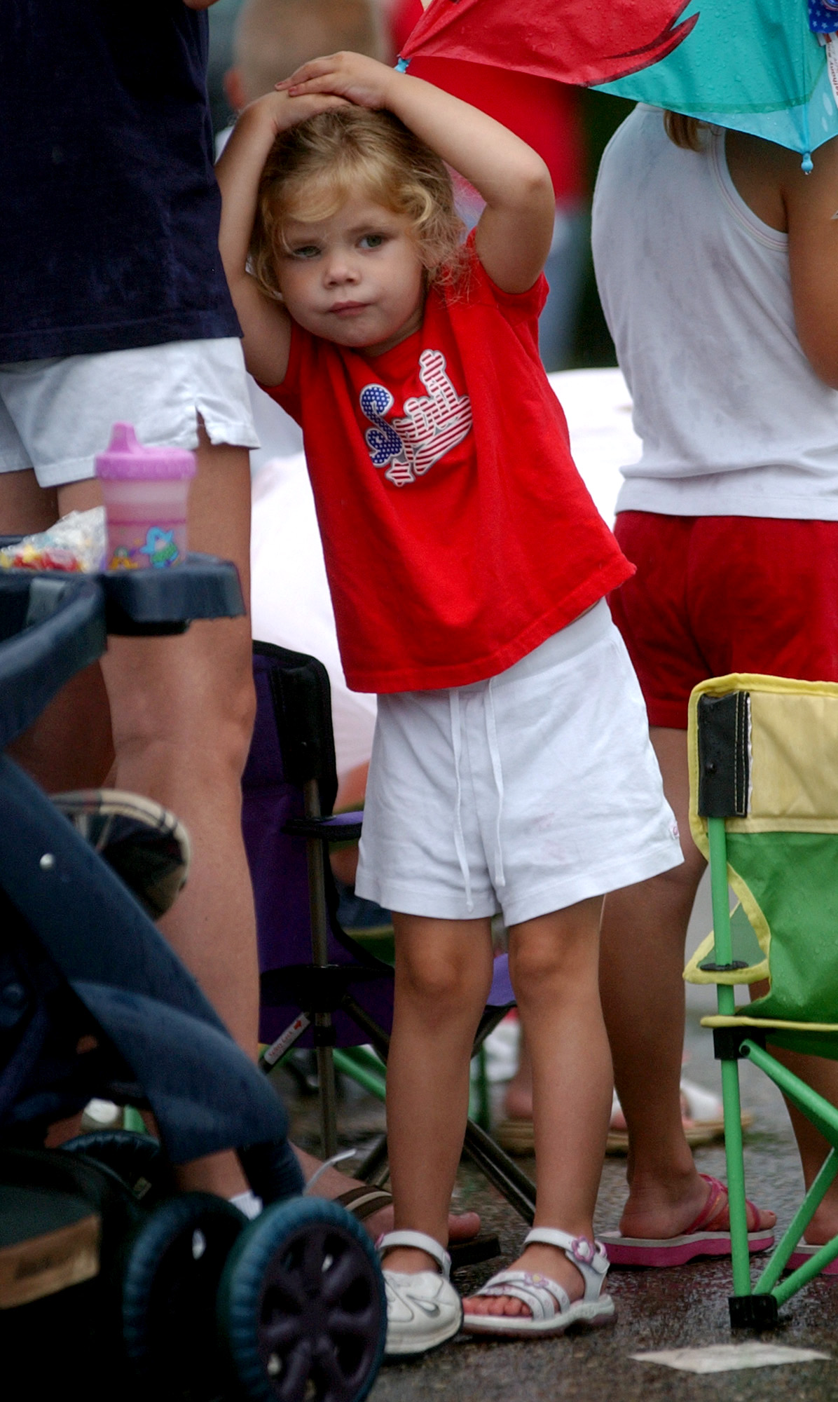 Sydney Bost((cq)), 2, tries to keep the raindrops from falling on her head during the 4th of July Festival Parade Tuesday, 07/04/06. Staff photo by E.L. Hubbard
